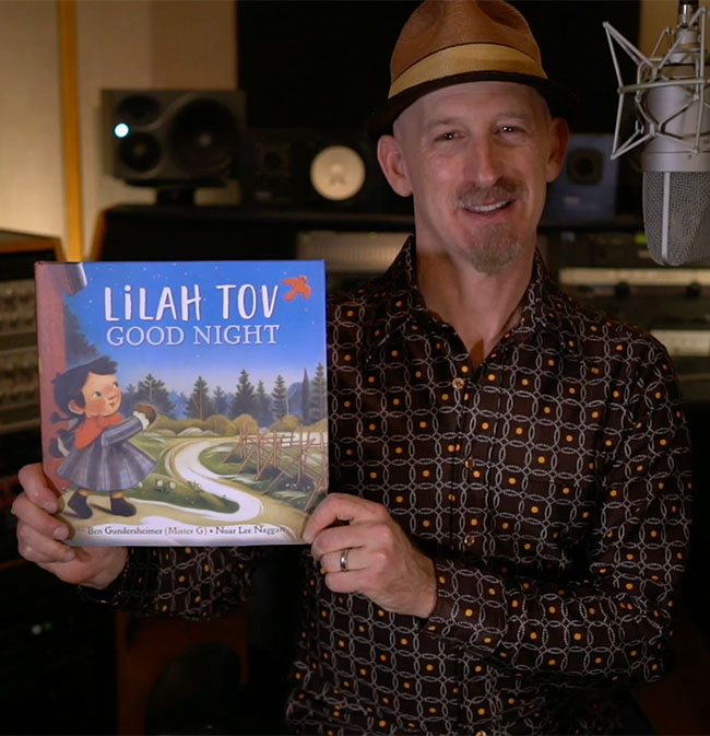 Mister G holds a copy of the book Lilah Tov