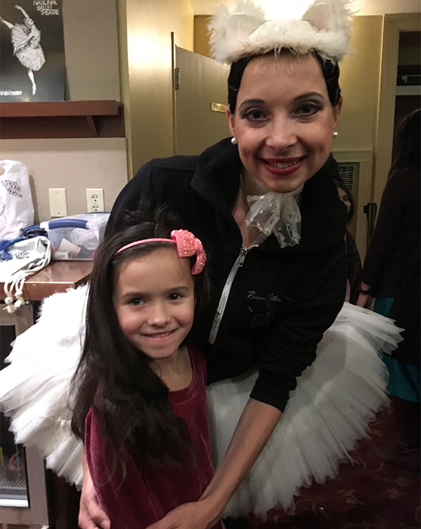 Ballerina smiling with a little girl.